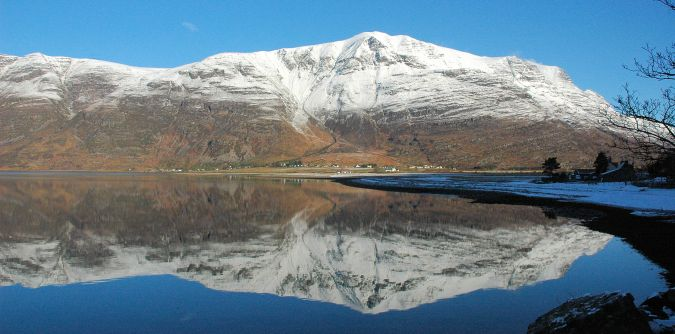 This view shows a snow-capped Liathach as seen on a bright February day. The photo was taken from the roadside at Annat.